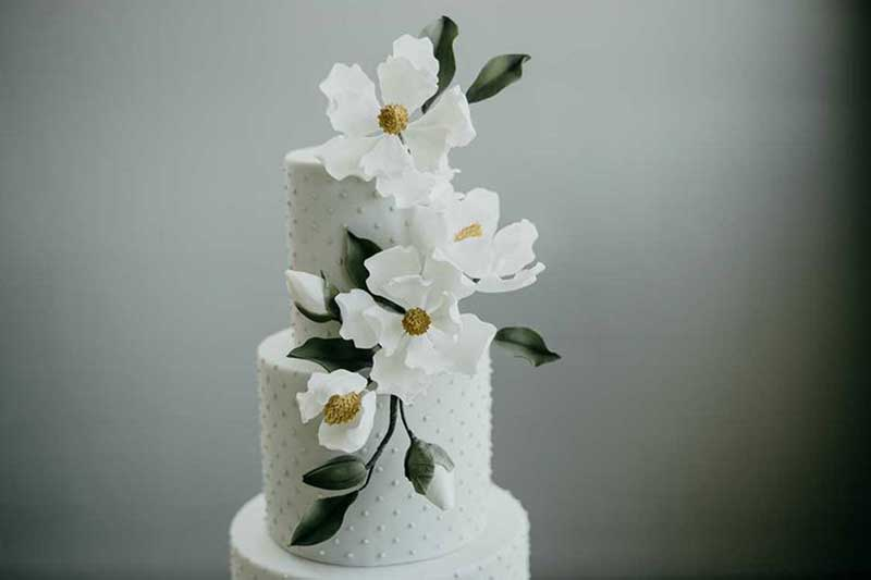 White wedding cake with white and yellow flowers