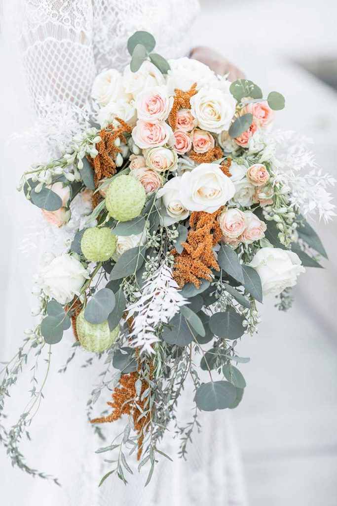 Bouquet with roses, eucalyptus, orange, and pink flowers
