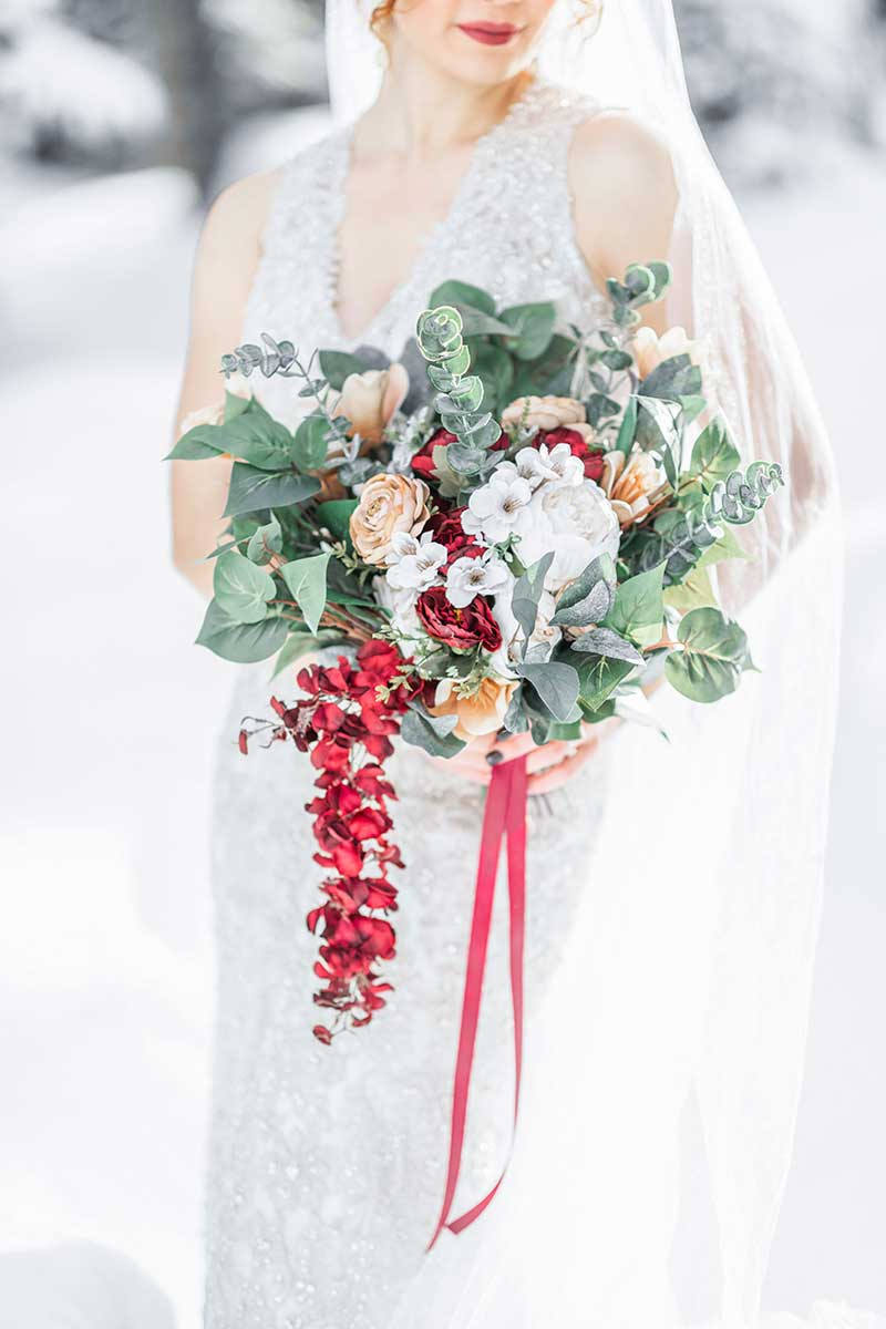 Winter bouquet with rose, eucalyptus, and pops of orange and red