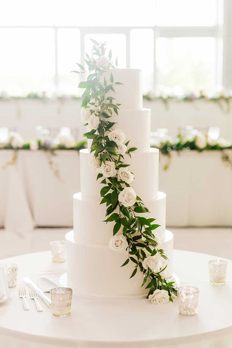 5-tier white wedding cake with live greenery and roses