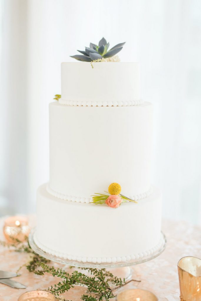 3-tier white wedding cake with succulent on top and beading between layers