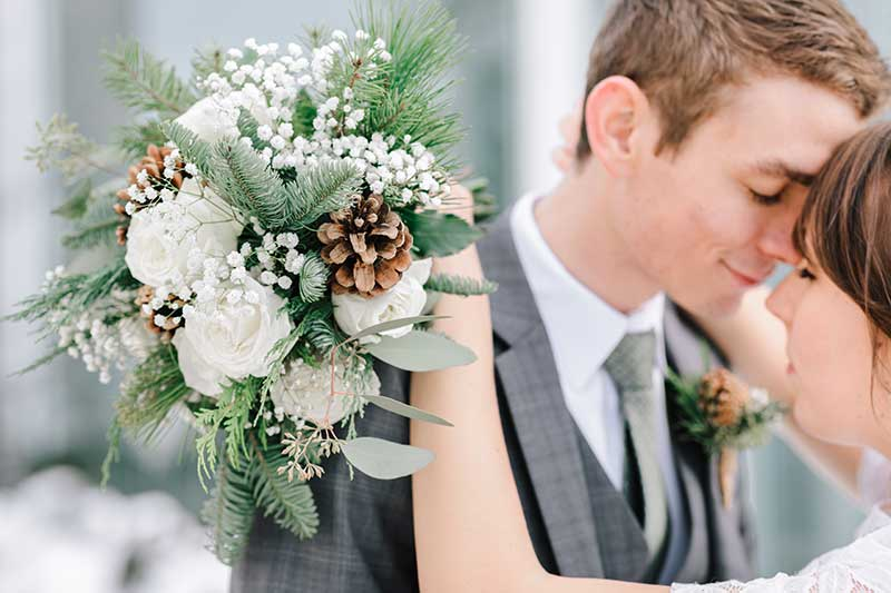 Winter bouquets with pine cones, roses, and pine needles