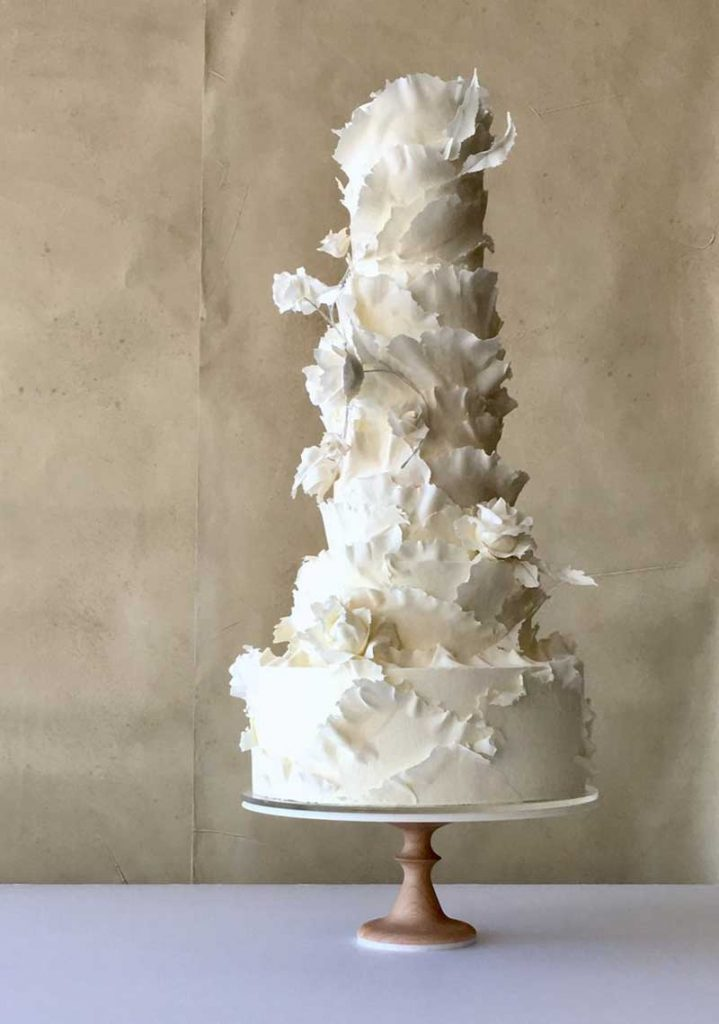 5-tier white wedding cake with thin paper flowers