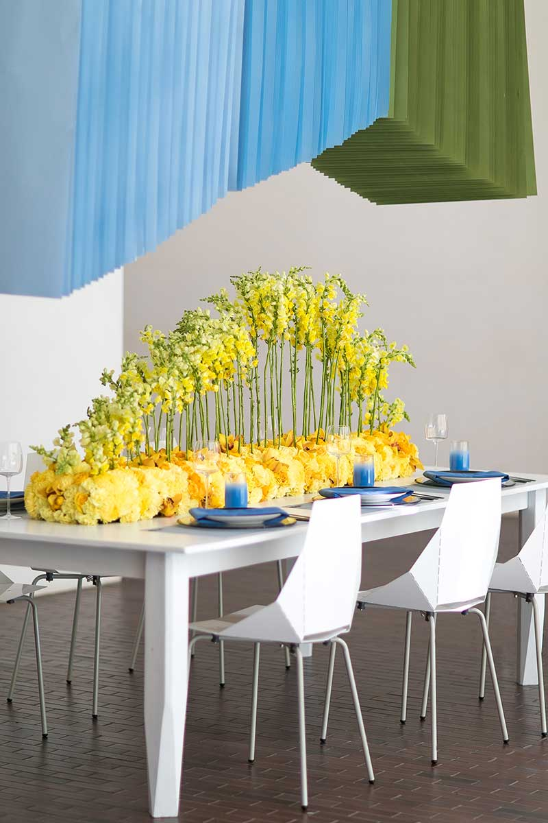 Modern wedding table with mod white chairs and yellow floral centerpiece