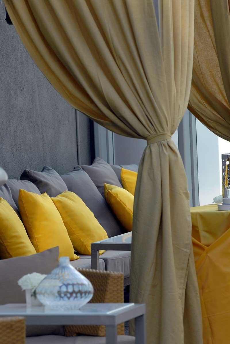 Wedding lounge with gray couch and yellow pillows