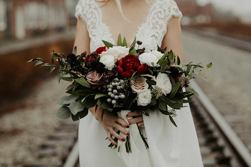 Moody wedding bouquet with red and white roses and berries