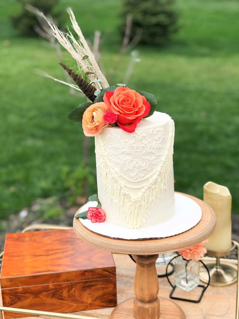Single-tier boho wedding cake with florals on top