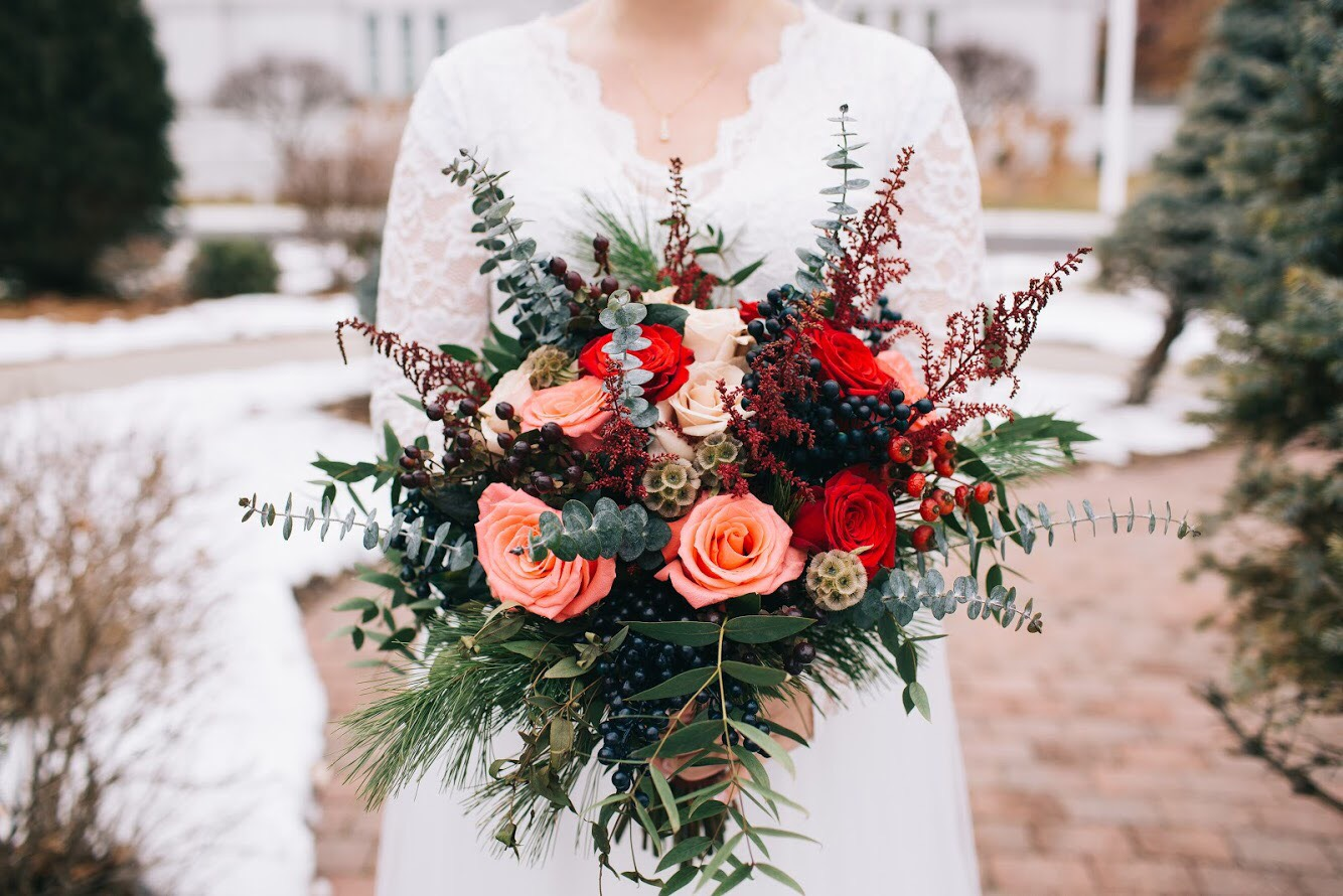 Pink, red, and greenery winter bouquet by Renning's Flowers