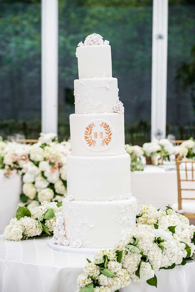 5-tier white wedding cake with floral details and gold monogram