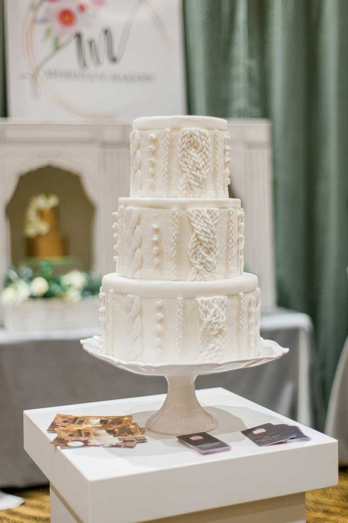 3-tier white wedding cake with piping resembling a sweater