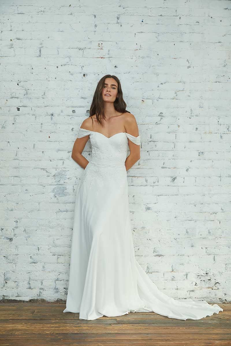 Bride in off the shoulder gown stands against white brick wall
