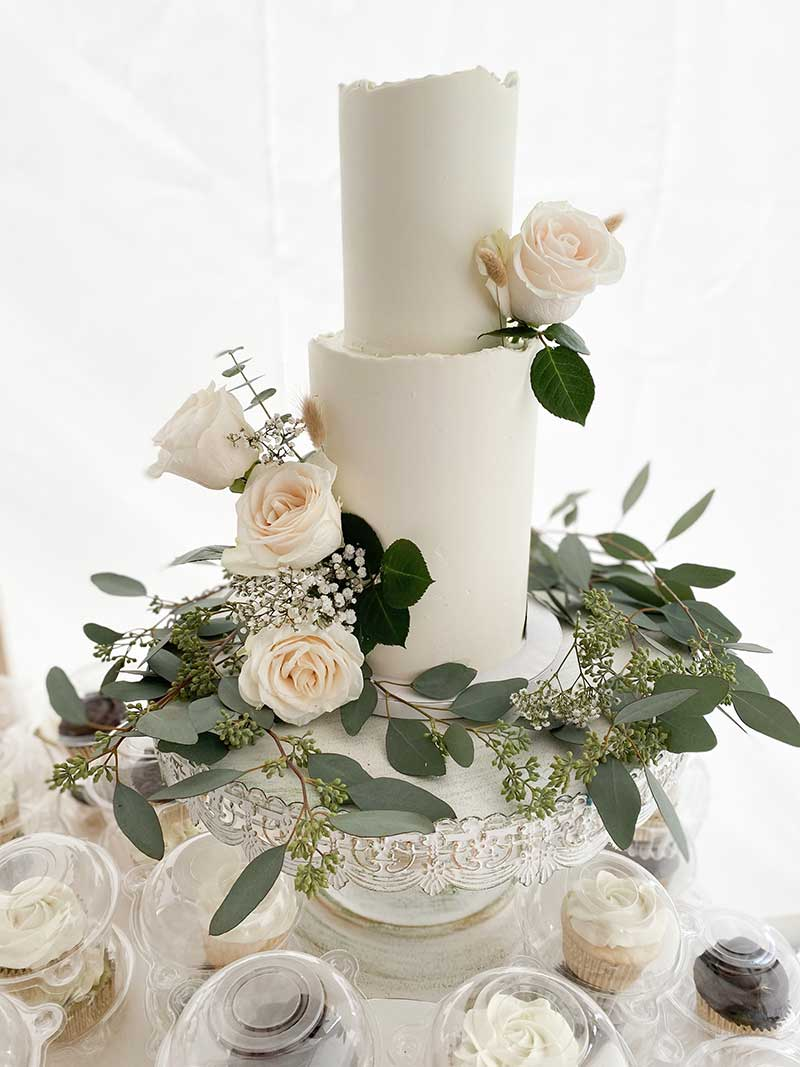 Smooth white wedding cake with greenery and roses