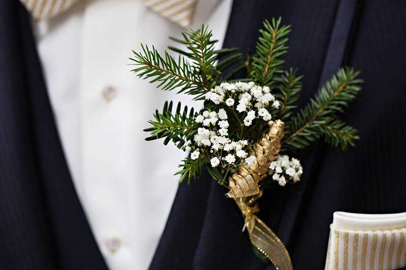 Winter boutonnière with gold wrap, baby's breath, and pine