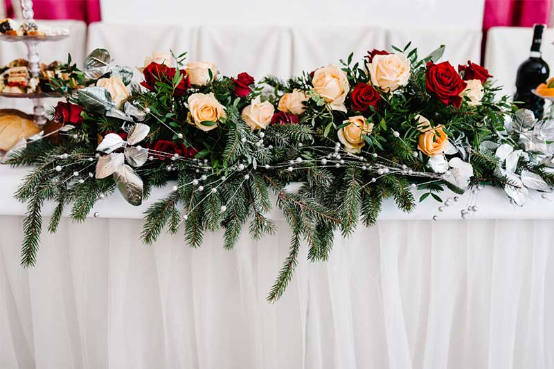 Tabletop floral garland with red and peach roses and berries
