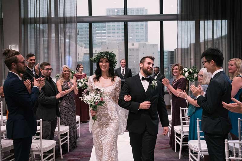 Couple walks down aisle at hotel wedding venue J. Powers