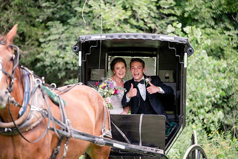 Bride and groom ride in horse drawn carriage at Sacred Clay Inn wedding