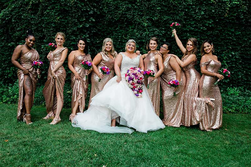 Bride in tulle ballgown poses with 8 bridesmaids in sequin rose gold gowns
