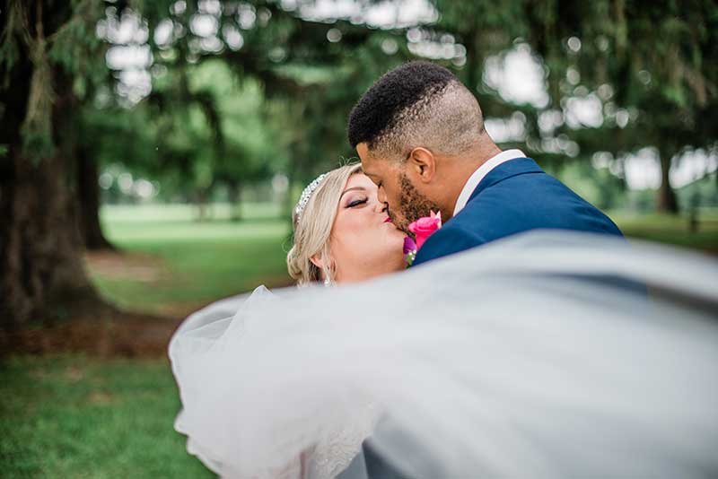 Bride and groom kiss as veil flows in the wind