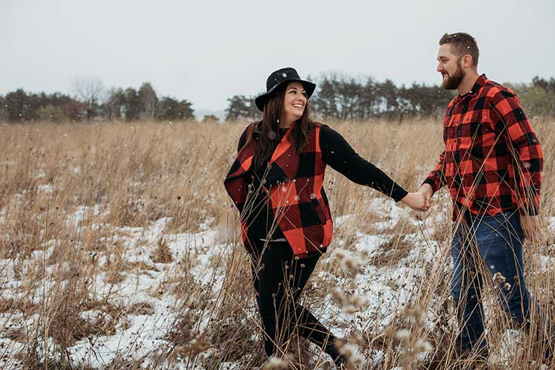 Engaged couple walks through field in red and black buffalo check tops
