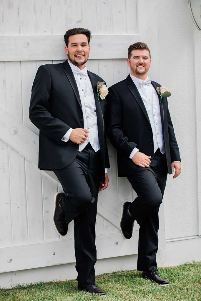 Two grooms in black suits lean up against a white barn door