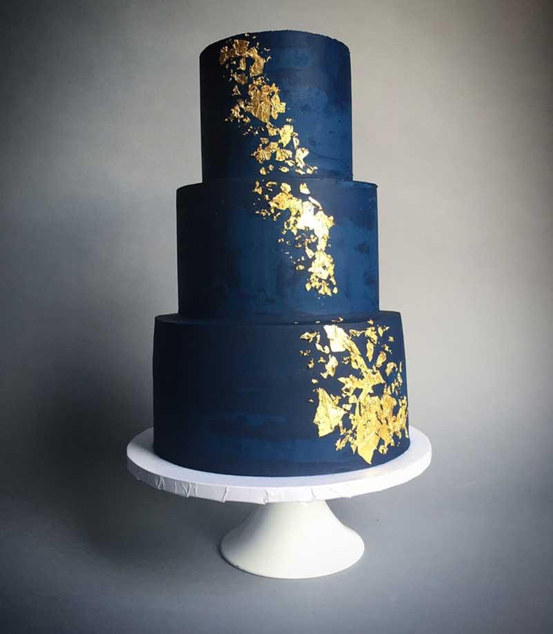 Navy blue 3-tier wedding cake with gold metallic flakes
