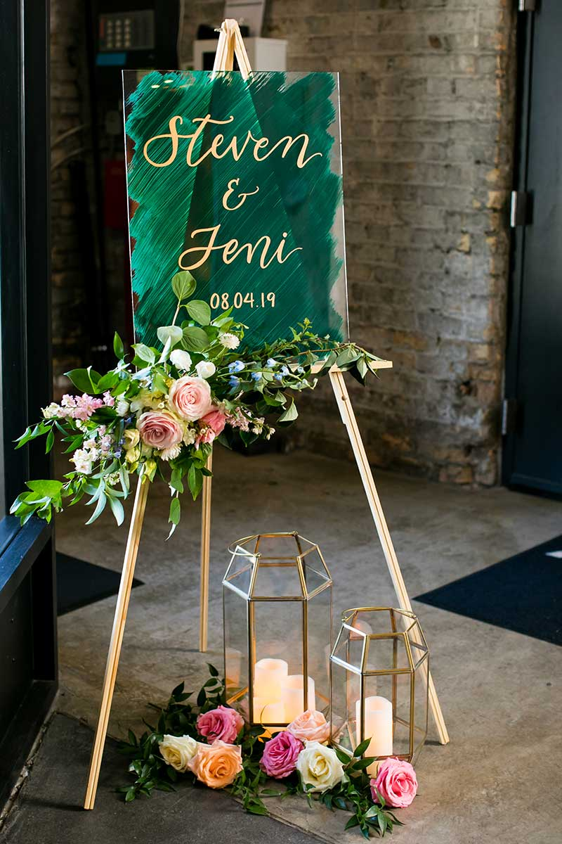Dark green wedding welcome sign with gold calligraphy writing