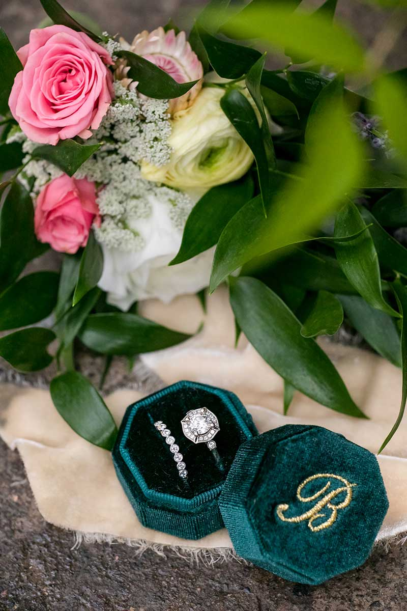 Wedding engagement ring and band sit inside a velvet green box