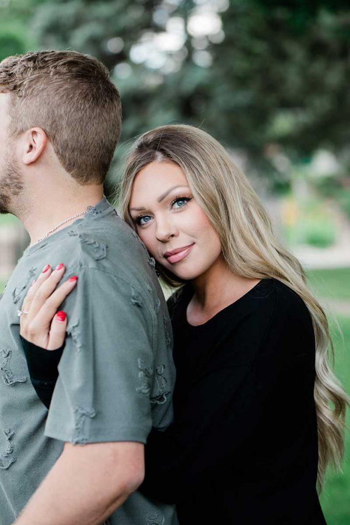 Woman lays head on fiances back