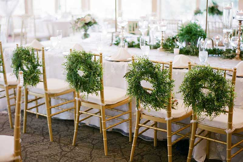 Gold chivari chairs with green wreaths hanging on back