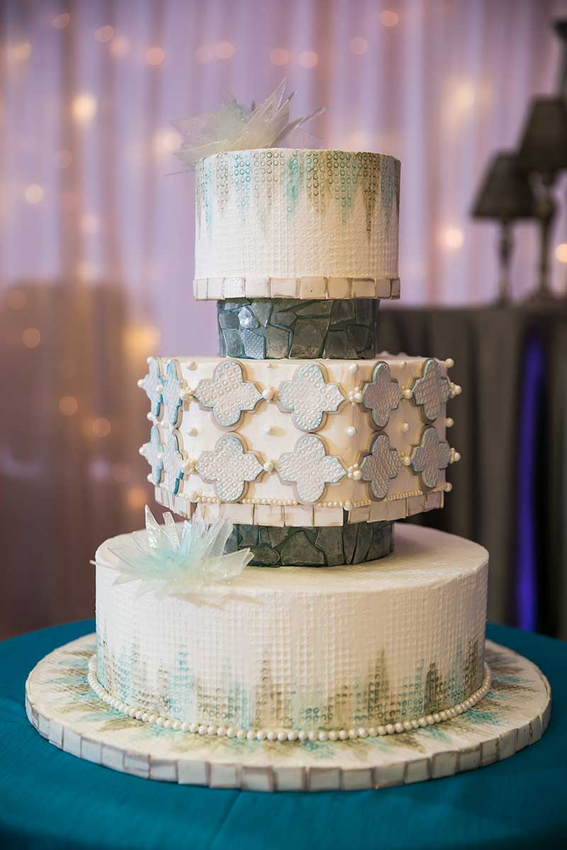 3 tier white wedding cake with gold and blue detailing