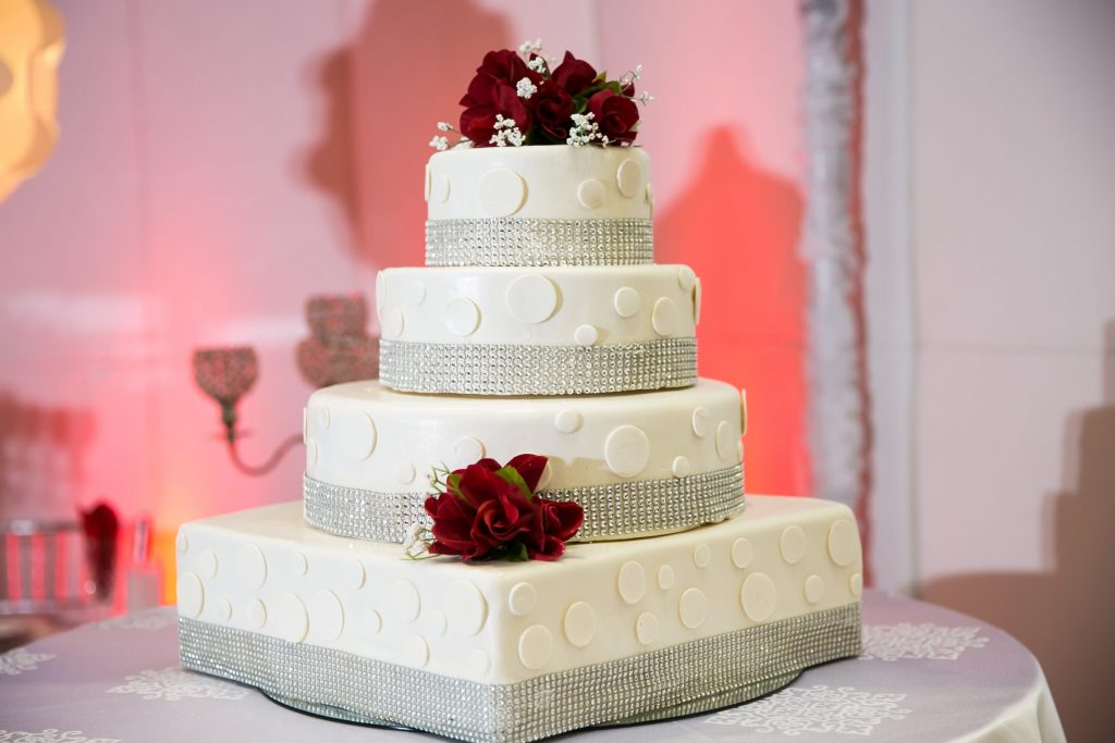 White wedding cake with white dots and red flowers