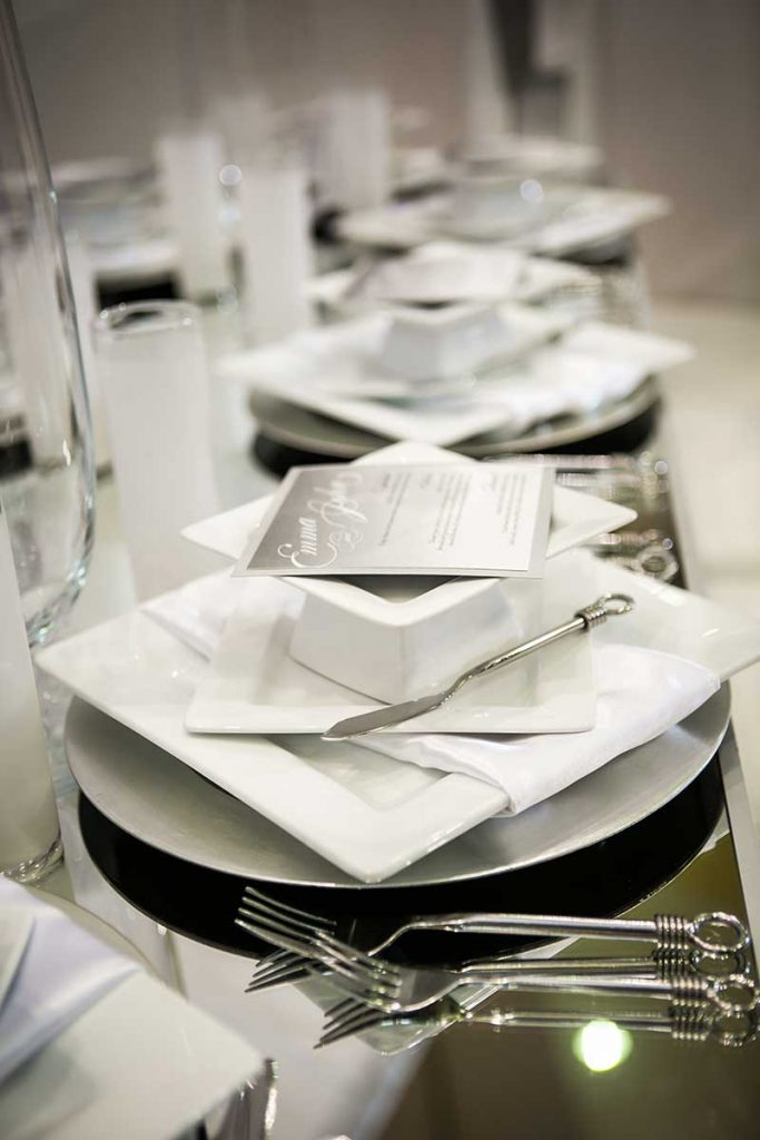 All white wedding tabletop decor with plates, silverware, napkins, and a menu at winter inspiration stations