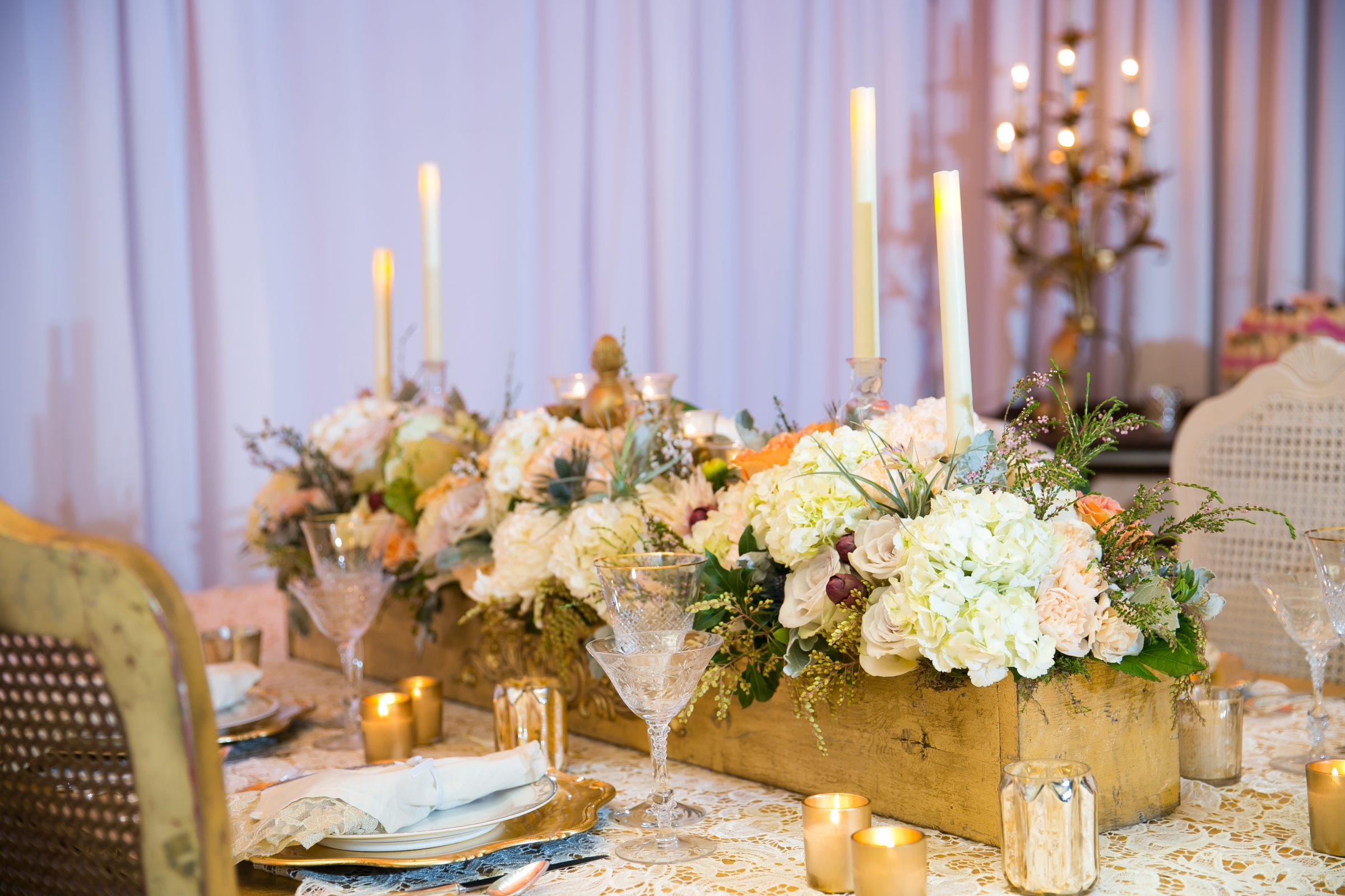 Rustic wood wedding centerpiece with greenery and white floral inside