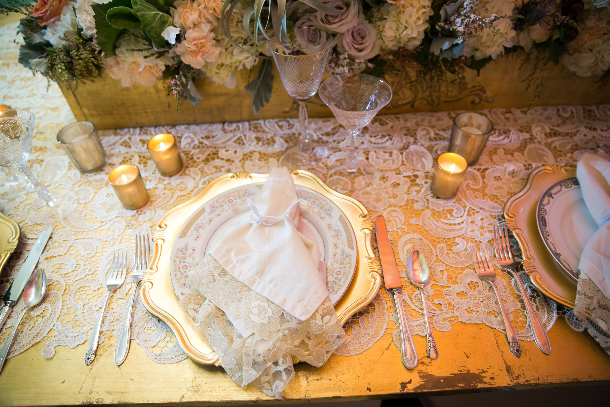 Gold wedding charger with vintage plate and napkin on top
