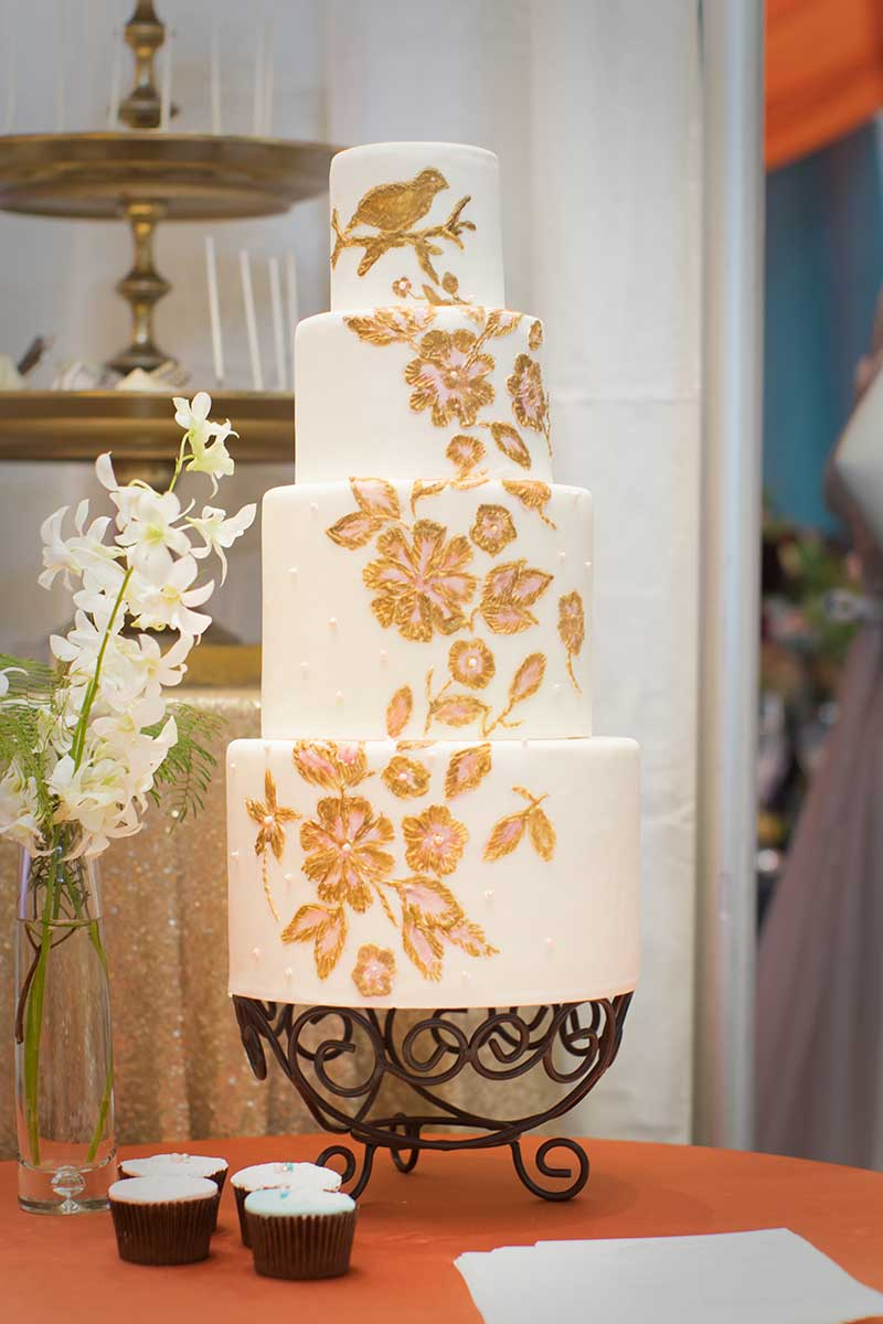 4-tier white wedding cake with gold painted flowers
