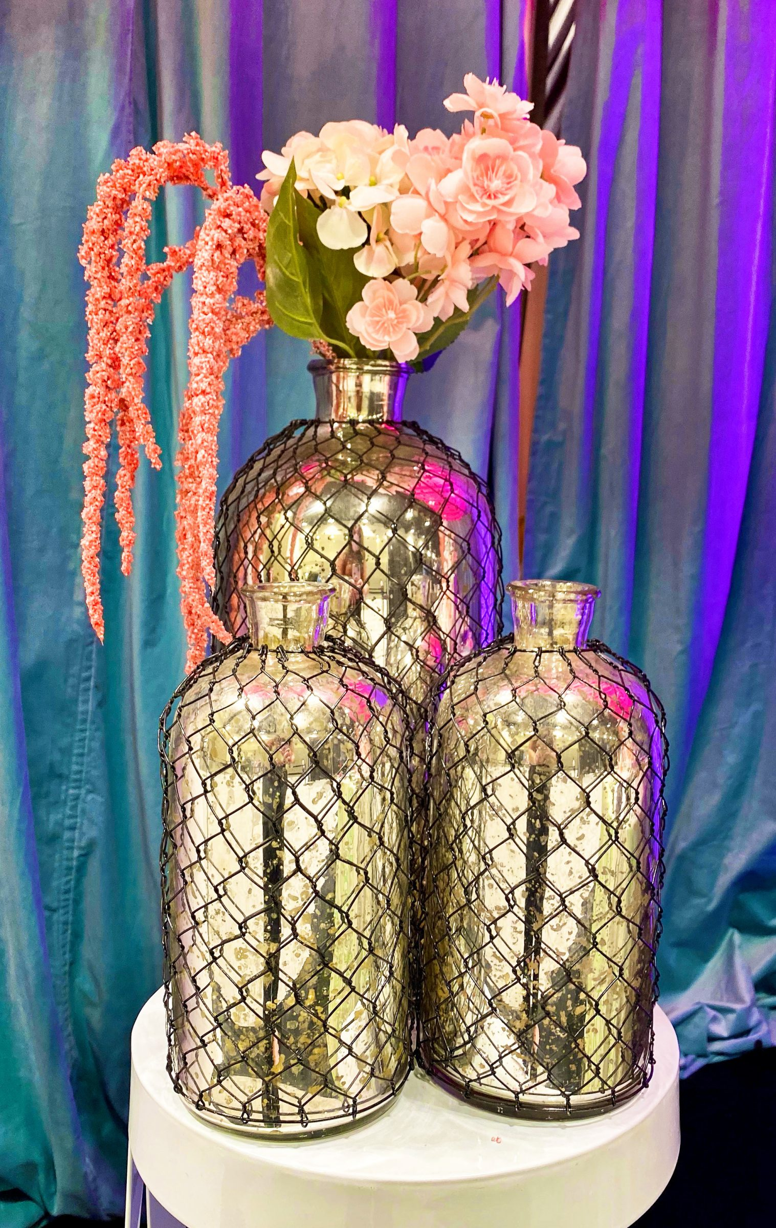 Tall gold vases in black cages with pink and blue flowers