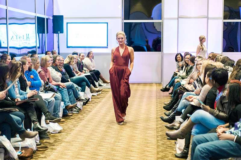 Model walks runway in maroon bridesmaid jumpsuit