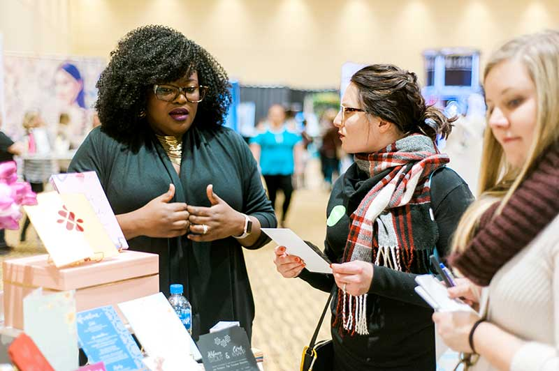 Bridal show vendor talks to bride at Unveiled Rochester 2021