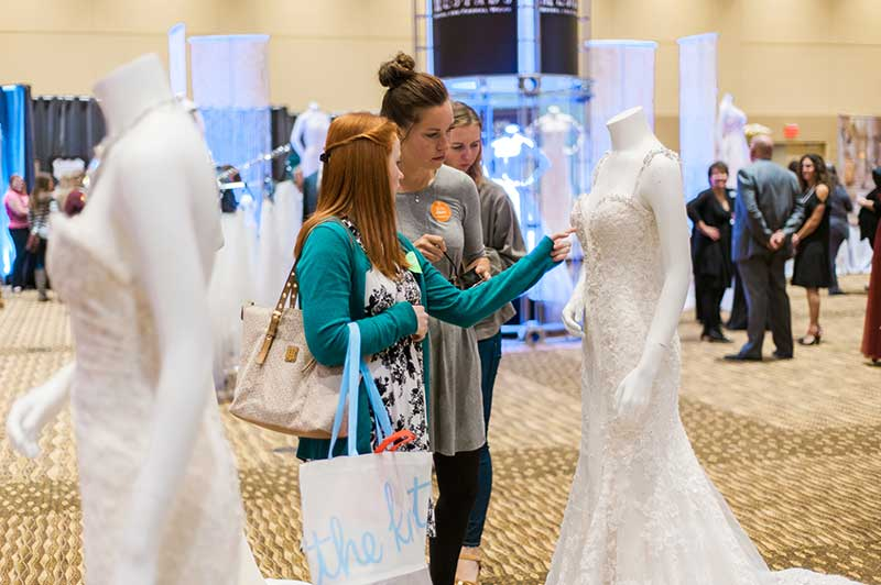 Bride looks at dresses at Unveiled Rochester 2021