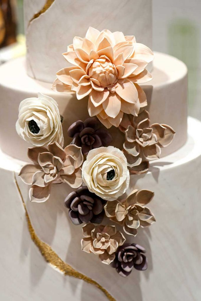Paper flower wedding cake with blush, beige, and white flowers