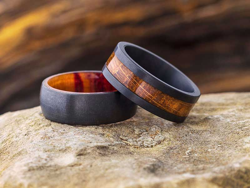 Two wedding rings with black zirconium and wood by Jewelry by Johan