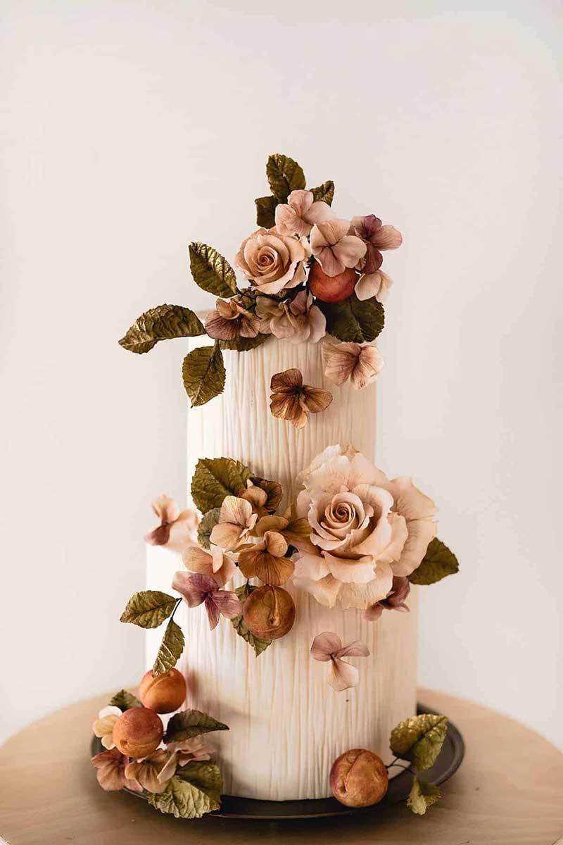 Intricate white wedding cake with dark green, orange, and blush sugar flowers