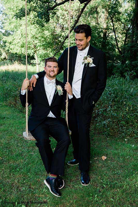 Groom pushes groom on swing at outdoor wedding