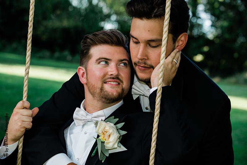 Grooms pose on swing that hangs from tree at outdoor wedding in MN