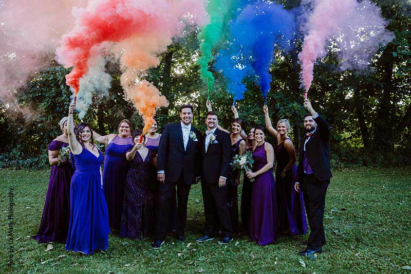Bridal party holds rainbow smoke bombs as grooms kiss
