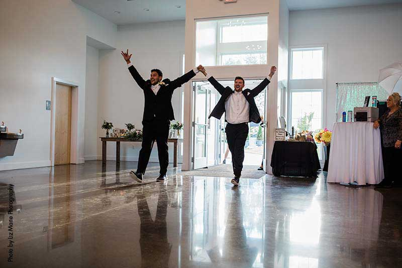 Grooms walk into wedding reception inside updated contemporary barn wedding venue