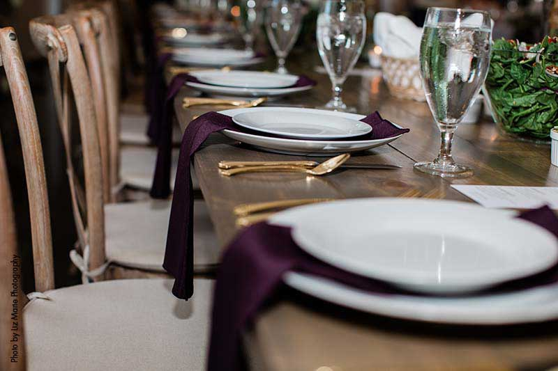 White plate and charger with plum napkin and gold flatware