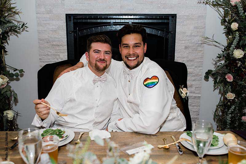 Grooms pose for photo at reception with heart pride patch sewn in on white button up shirts