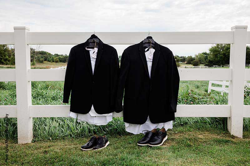 Grooms' suit and suits sit on fence