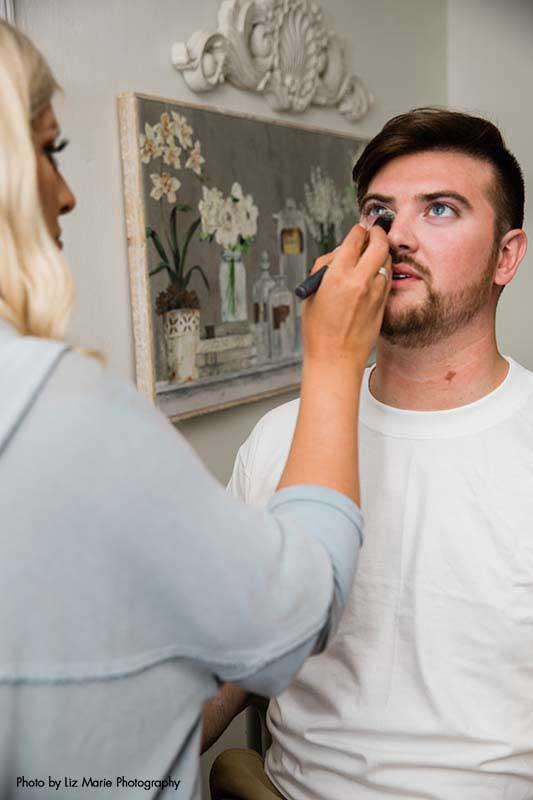 Groom gets makeup done before modern outdoor wedding